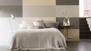 La peinture de la chambre contribue à créer une ambiance. Ici elle se veut reposante et hyper originale grâce à des rectangles dans un camaïeu de beige et de gris.