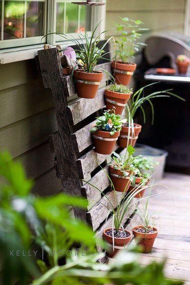 Un mur végétal n'est pas compliqué à composer : avec une palette et quelques plantes en pot, votre déco balcon se métamorphose en quelques minutes pour une touche de nature.