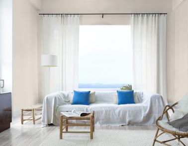 Un salon qui ne manque pas de luminosité grâce à la peinture à la chaux qui habille les murs subtilement. Une déco et une couleur douce pour un salon au caractère unique
