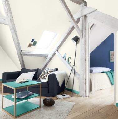 La peinture de cette chambre sous combles est ponctuée par de belles poutres en bois massif blanchies pour faire propre. Le mur du fond peint en bleu donne du caractère.