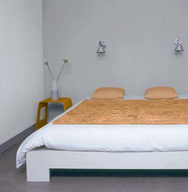 La peinture de cette chambre parentale confère une ambiance tranquille dans une pièce très contemporaine rehaussée de bois et d'accessoires déco aux tons chauds.