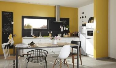 La peinture jaune donne de la lumière dans cette cuisine blanche spacieuse. Les tableaux et le mobilier noirs apportent du contraste pour un caractère bien trempé.