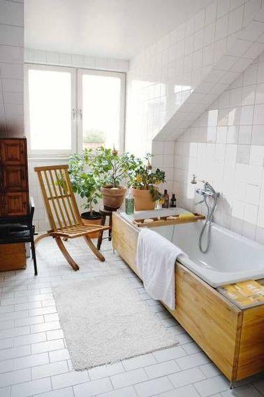 Lorsque l'on refait sa salle de bain recouvrir le tablier de la baignoire avec du bois, par exemple du bambou ou du teck apporte de la chaleur dans un espace tout blanc. Ajouter une chaise, un petit meuble en bois et le décor est parfait