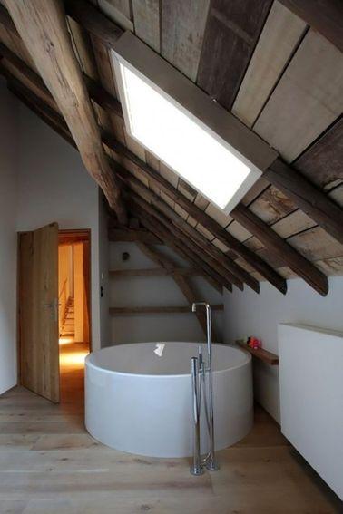 Une salle de bain en longueur aménagée sous de magnifiques combles avec  baignoire îlot ronde posée sur un parquet salle de bain en teck