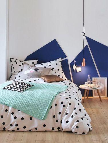 Une tête de lit géométrique avec du linge de lit à pois