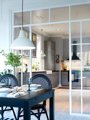 Au lieu de séparer les deux pièces, cette verrière intérieure souligne la cuisine et la salle à manger avec classe. On a d'ailleurs choisi d'avoir une continuité sur le parquet massif blanc.
