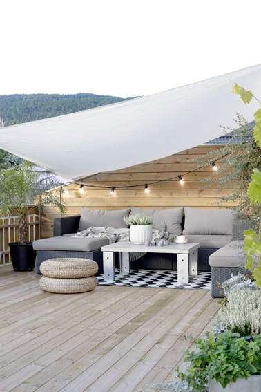 Le voile d'ombrage c'est l'accessoire incontournable de l'été pour se prélasser à l'extérieur. Aménagée sous un voilage blanc, cette terrasse se fait déco et accueillante