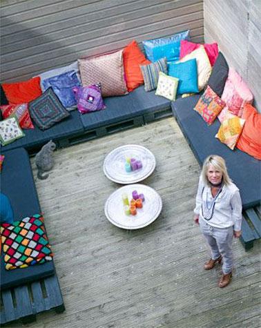 Un salon de jardin aménagé en u avec un grand canapé en palette sur cette terrasse en bois ! Un endroit confortable qui invite à la convivialité pour les soirées d'été