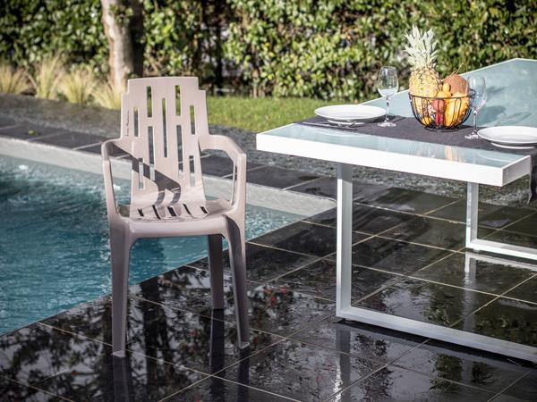 Une chaise design de couleur taupe s'invite au bord de la piscine pour une déco extérieur très tendance