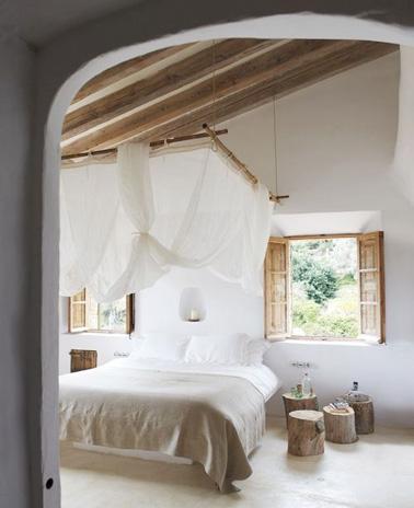Une chambre d'une grande élégance grâce à un ciel de lit ultra chic suspendu aux poutres apparentes. Des tables de nuits en rondins de bois et voilà une chambre 100% campagnarde