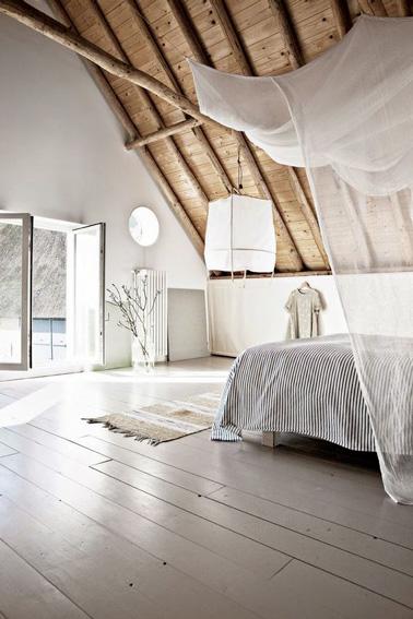 Parquet, couleurs claires, descente de lit, lanterne et ciel de lit s'associent pour une déco ultra zen dans la chambre parentale et son petit balcon ouvert sur le jardin