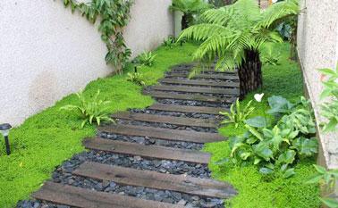 Pas japonais fait avec des traverses en bois de recup sur du gravier noir, pour aménager l'allée du jardin dans une ambiance tropicale avec la mousse et les fougères.