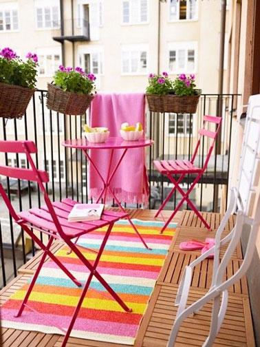 Sur ce balcon au sol en caillebotis bois clair, la couleur rose fait sa star ! Table et chaises de jardin font un clin d'oeil aux fleurs, au tapis et au plaid pour une déco vive