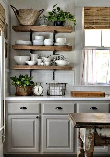 Avec de belles étagères en bois, on mise sur le style rustique pour cette cuisine en bois à la déco grise et au plan de travail blanc dans une maison de campagne !