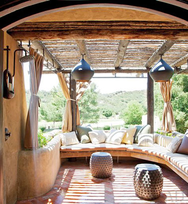 Une terrasse esprit lounge avec un grand canapé confortable, des cannisses pour se protéger du soleil et des rideaux pour créer un coin intime à l'extérieur