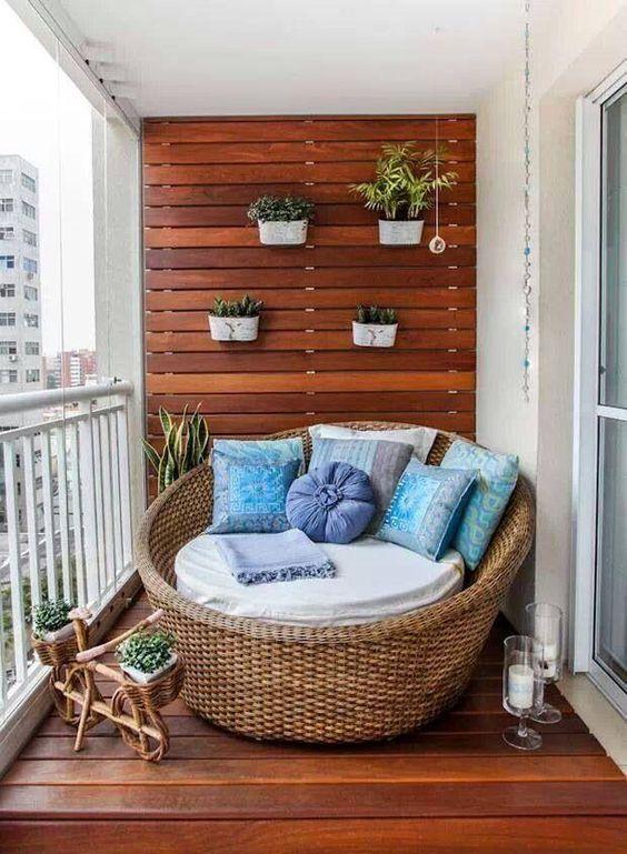 Le bleu et le bois font bon ménage sur ce balcon ! Le magnifique fauteuil en osier accueille des coussins bleu pastel qui donnent une touche de couleur à la déco