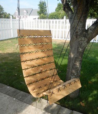 Un fauteuil suspendu à faire en palette pour profiter du jardin sous un arbre. Suspendu à une poutre ce fauteuil trouve une place sur la terrasse ou le balcon
