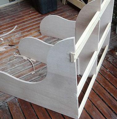 Début du montage du banc de jardin avec un design de contreplaqué courbés et les planches de pin fixés sur les trois fentes derrière les supports de contreplaqué.