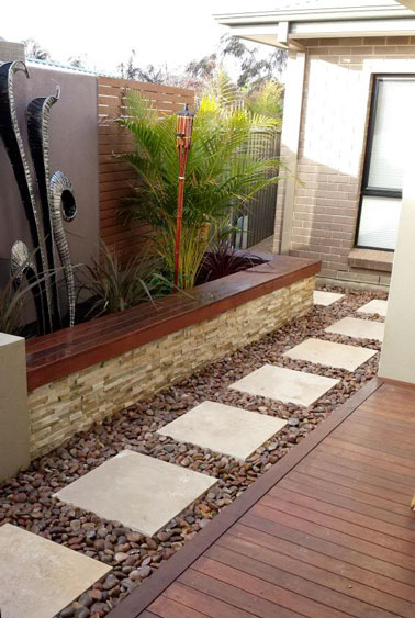 Une élégante allée de jardin fait à partir de pas japonais composé de pavés de pierre blanc cassé sur du gravier de cailloux sombres en accord avec la déco de la terrasse.