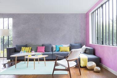 Un salon chic avec un mur peint en rose et une peinture couleur parme recouvrant un autre mur. Une déco pimpante soulignée par des coussins colorés et le parquet