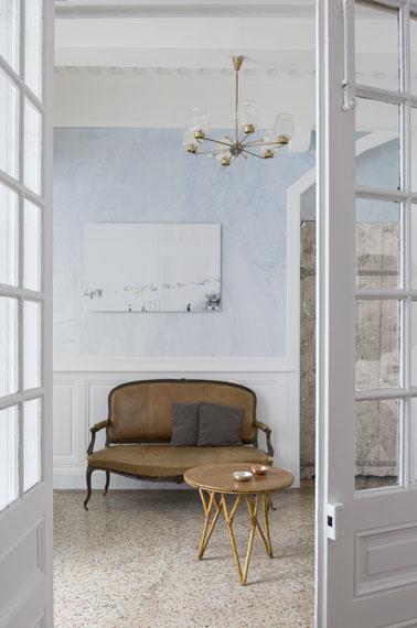 En voilà une entrée coquette ! Du stuc bleu vénitien appliqué sur les murs, un lustre et un canapé antique pour une déco qui ne manque pas de classe et d'allure