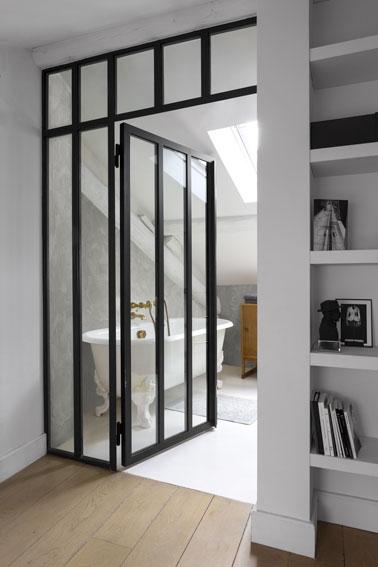 Une salle de bain sous pente élégante avec une verrière intérieure qui allie baignoire sabot et murs en stuc gris pour un rendu rétro et hyper coquet !
