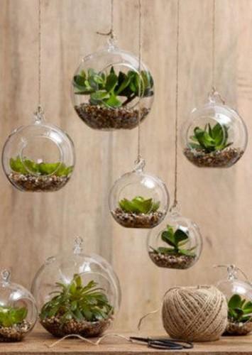 Des terrariums composés de gravier et de plantes suspendus à l'aide d'un fil pour une touche nature dans une déco intérieure. Attention à la lumière pour les plantes.