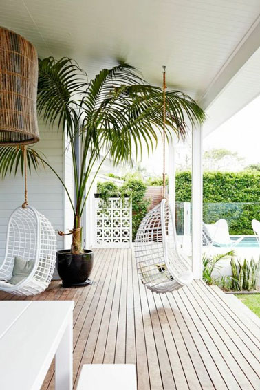 Les fauteuils suspendus sous le proche de cette terrasse en bois permettent de se balancer confortablement à l'ombre tout en contemplant la piscine et le jardin, top !