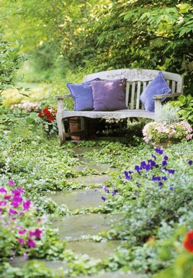 Romantique comme tout, un petit banc a été placé au bout d'une allée en pierre dans le jardin pour une déco bucolique et agréable au milieu des fleurs et de la verdure