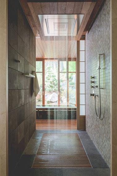 Avec vue sur le jardin, cette salle de bain esprit spa aménagée à la fois avec une baignoire et une douche italienne assure des moments pour soi 100% détente