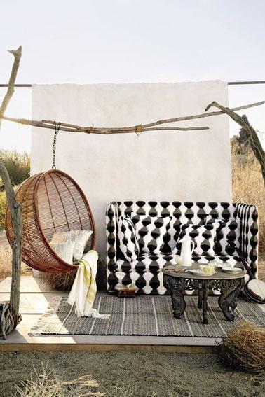Sur cette terrasse, on a misé sur un mixe des genres pour un rendu hyper déco ! Un espace de détente assuré par un fauteuil suspendu cocon et un beau canapé