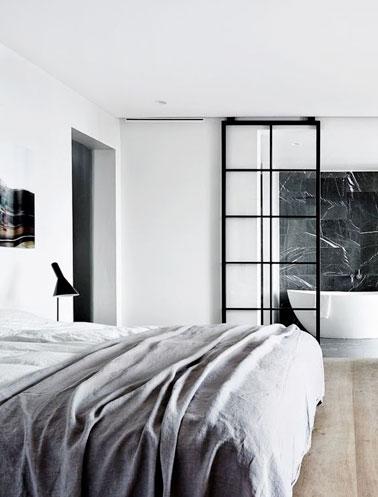 Cette chambre parentale moderne accueille une porte coulissante en verre au style d'une verrière intérieure réalisée par un ferronnier et montée sur rail, top la déco !