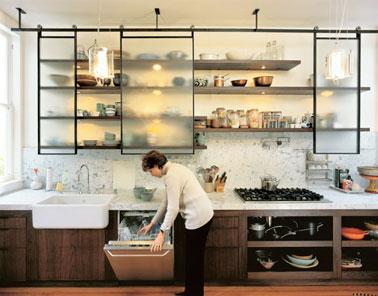 Voilà une cuisine industrielle ultra stylée réalisée avec des portes coulissantes vitrées et spécialement aménagées pour masquer le contenu des étagères !