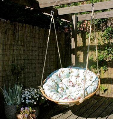 Accroché à l'aide de cordes sur le patio, ce fauteuil suspendu rond ultra moelleux fait office de petite balançoire sur la terrasse idéal pour faire bronzette