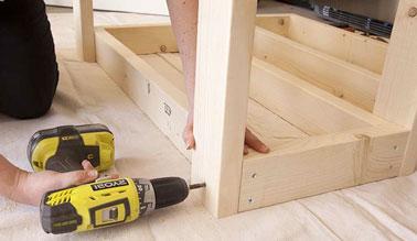 Alt : Avec des tasseaux de bois de 4x6 cm, fixer les pieds de la desserte à chaque extrémité d'un des cadres et ensuite, le retourner pour fixer l'autre cadre aux pieds.
