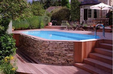 Aménagée en contrebas de la terrasse en bois, cette charmante piscine hors sol sertie de pierre et de bois au style authentique sublimera votre déco extérieure