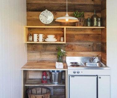 Dans la petite cuisine, on mise sur des planches de bois en crédence et en plan de travail pour la déco ! Une kitchenette aux rangements multipliés qui a du style