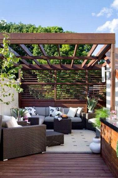 Confort absolu sur cette petite terrasse aménagée avec une pergola et un brise-vue en bois permettant de faire la sieste tranquillement sur le canapé de jardin