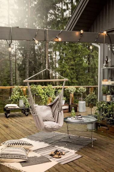 Pleine de verdure, cette terrasse en bois rassemble les éléments déco zen ! Un fauteuil suspendu hyper confortable offre un espace de détente sans pareil à l'extérieur