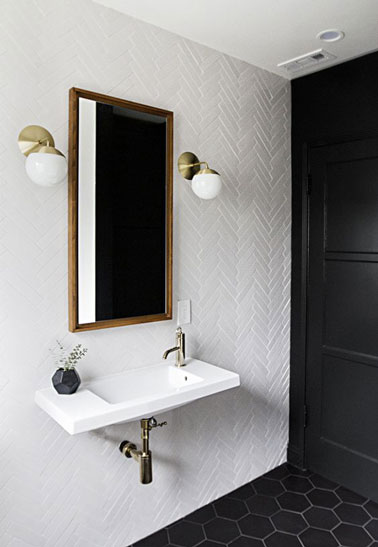 Style vintage dans cette jolie salle de bain blanche au sol en tommettes de couleur noir décorée d'un beau miroir et de deux appliques murales blanches et dorées