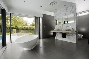 Avec un carrelage gris anthracite et un délimiteur aspect marbre, cette salle de bain a tout de design ! Une déco soulignée par une baignoire îlot, c'est top !