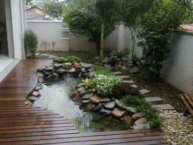 Complètement intégré à la terrasse en bois et prenant place juste à côté de l'allée de jardin, ce petit bassin décoré de pierre trouve naturellement sa place
