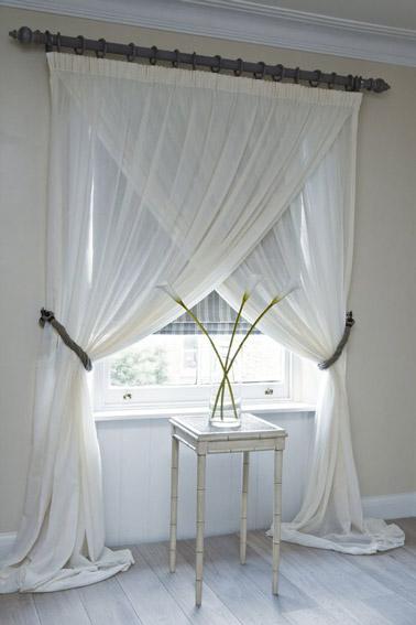 Voilà une idée qui sort de l'ordinaire ! Dans cette chambre blanche, les rideaux blancs ont été croisés afin de donner de l'originalité à la pièce et laisser entrer la lumière