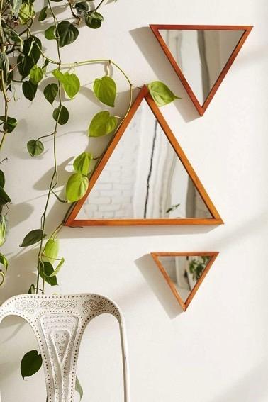 Des petits miroirs en formes de triangles sont joliment disposés sur un mur blanc de façon déco afin de donner du dynamisme et un certain cachet à la pièce
