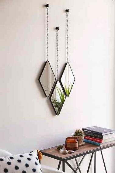 Une touche déco hyper charmante donnée par trois petits miroirs en forme de losanges suspendus à des chainettes apportent de l'originalité à la chambre !