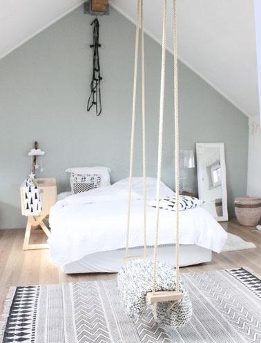 Ambiance de douceur dans cette chambre originale où une balançoire s'est invitée dans la déco avec un plafond blanc cassé, des murs gris perle et un parquet blanc