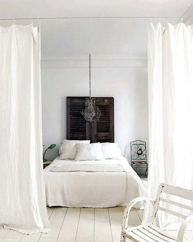 Cette chambre blanche ultra originale adopte la déco récup pour une ambiance chic et élégante ! Des voilages complètent la déco ainsi qu'une tête de lit faite avec des volets
