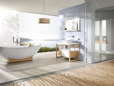 La salle de bain adopte une ambiance déco naturelle grâce à des couleurs neutres, une baignoire îlot et du bois. Moments de relaxation assurés dans le bain !