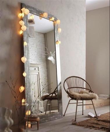 Encadré d'une guirlande lumineuse, ce long miroir vertical en bois vieillit apporte une ambiance scintillante et complète la déco d'inspiration scandinave