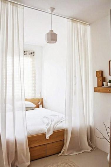 Le lit placé dans un recoin de cette chambre parentale blanche et bois constitue un espace bien délimité par des voilages afin de créer un espace intime à part